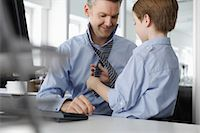 father with two sons not girls - Son putting tie on father at desk Stock Photo - Premium Royalty-Freenull, Code: 649-07119813