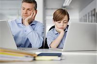 Father and son using laptops looking bored Stock Photo - Premium Royalty-Freenull, Code: 649-07119816