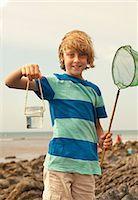 Teenage boy holding jar and fishing net Stock Photo - Premium Royalty-Freenull, Code: 649-07119903