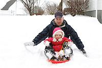 A father and his three year old daughter sledding. Stock Photo - Premium Royalty-Freenull, Code: 6106-07120029