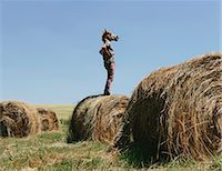 funny looking people - A Man Wearing A Horse Mask, Standing On A Hay Bale, Looking Out Over The Landscape. Stock Photo - Premium Royalty-Freenull, Code: 6118-07122118