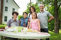 A Summer Family Gathering At A Farm. Five People Posing Beside The Table, Where A Child Is Making Fresh Lemonade. Stock Photo - Premium Royalty-Freenull, Code: 6118-07122160