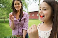 preteen open mouth - Family Party. A Child With A Fresh Cherry Between Her Teeth. A Young Woman Watching Her And Laughing. Stock Photo - Premium Royalty-Freenull, Code: 6118-07122180