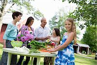 Family Party. A Table Laid With Salads And Fresh Fruits And Vegetables. Parents And Children. Two Girls, One Young Woman And A Mature Couple. Stock Photo - Premium Royalty-Freenull, Code: 6118-07122184
