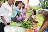 preteen kissing - Family Party. A Table Laid With Salads And Fresh Fruits And Vegetables. Parents And Children. A Mother Kissing A Daughter On The Cheek. Stock Photo - Premium Royalty-Freenull, Code: 6118-07122187