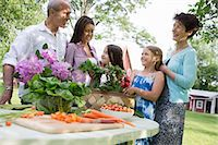 Family Party. A Table Laid With Salads And Fresh Fruits And Vegetables. Parents And Children. Stock Photo - Premium Royalty-Freenull, Code: 6118-07122190