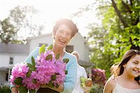 Family Party. A Woman Carrying A Large Bunch Of Rhododendron Flowers, Smiling Broadly. Stock Photo - Premium Royalty-Freenull, Code: 6118-07122197