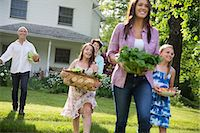 Family Party. Parents And Children Walking Across The Lawn Carrying Flowers, Fresh Picked Vegetables And Fruits. Preparing For A Party. Stock Photo - Premium Royalty-Freenull, Code: 6118-07122202