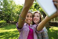 preteen touch - Two Girls Sitting Outdoors On A Bench, Using A Digital Tablet. Holding It Out At Arm's Length. Stock Photo - Premium Royalty-Freenull, Code: 6118-07122219