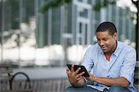 Summer In The City. People Outdoors, Keeping In Touch While On The Move. A Man Sitting On A Bench Using A Digital Tablet. Stock Photo - Premium Royalty-Freenull, Code: 6118-07122301