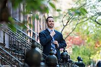 A Man In A Business Suit Adjusting His Tie. At The Bottom Of The Steps Of A Townhouse In A Terrace. Stock Photo - Premium Royalty-Freenull, Code: 6118-07122482