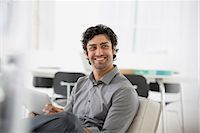 east indian (male) - Business. A Man Seated Smiling And Holding A Digital Tablet. Stock Photo - Premium Royalty-Freenull, Code: 6118-07122559