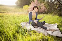 scenic and spring (season) - A Young Woman Sitting In A Field, On A Blanket, Holding And Looking At The Screen Of A Digital Tablet. Working Outdoors. Stock Photo - Premium Royalty-Freenull, Code: 6118-07122741