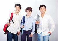 Three cheerful teenagers isolated on white background, back to school, best friends classmates, preteens standing and smiling  with backpacks and textbooks, knowledge and education concept Stock Photo - Royalty-Freenull, Code: 400-07123462
