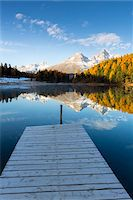 fall trees lake - Jetty at Lake Staz with Larch Trees and Snow Covered Piz Nair Reflected in it in Autumn, Canton of Graubunden, Switzerland Stock Photo - Premium Royalty-Freenull, Code: 600-07143716