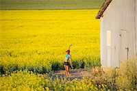 Young woman runner stretching in field of oil seed rape Stock Photo - Premium Royalty-Freenull, Code: 614-07146377