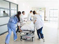 pushing - Doctors rushing patient on stretcher down hospital corridor Stock Photo - Premium Royalty-Freenull, Code: 6113-07146748