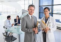 Portrait of smiling businessman and doctor in meeting Stock Photo - Premium Royalty-Freenull, Code: 6113-07146797