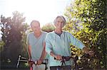 Senior couple walking bicycles in park