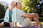 Senior couple sitting on yoga mat in park