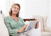Portrait of senior woman using digital tablet on sofa Stock Photo - Premium Royalty-Freenull, Code: 6113-07146924