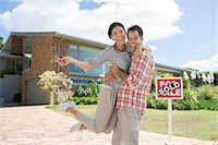 sold sign - Portrait of enthusiastic couple hugging outside house with For Sale sign Stock Photo - Premium Royalty-Freenull, Code: 6113-07147135
