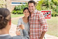 sold sign - Realtor giving couple keys to new house Stock Photo - Premium Royalty-Freenull, Code: 6113-07147148