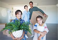 Portrait of smiling family holding belongings in new house Stock Photo - Premium Royalty-Freenull, Code: 6113-07147149