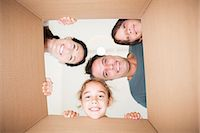 Family looking down at camera through cardboard box Stock Photo - Premium Royalty-Freenull, Code: 6113-07147167