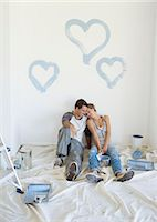 Couple painting blue hearts on wall Stock Photo - Premium Royalty-Freenull, Code: 6113-07147208