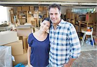 Portrait of smiling couple outside garage among cardboard boxes Stock Photo - Premium Royalty-Freenull, Code: 6113-07147241