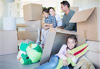 Family among cardboard boxes in livingroom Stock Photo - Premium Royalty-Freenull, Code: 6113-07147242