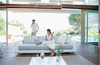 rich lifestyle - Couple using cell phone and laptop in living room Stock Photo - Premium Royalty-Freenull, Code: 6113-07147488