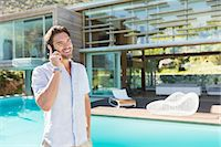 rich lifestyle - Man talking on cell phone at poolside Stock Photo - Premium Royalty-Freenull, Code: 6113-07147490