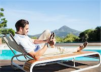 Man using digital tablet on lounge chair at poolside Stock Photo - Premium Royalty-Freenull, Code: 6113-07147494