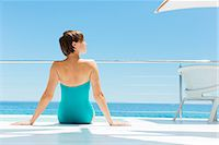 rich lifestyle - Woman relaxing poolside with ocean in background Stock Photo - Premium Royalty-Freenull, Code: 6113-07147511