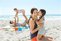 Girl kissing mother's cheek at beach Stock Photo - Premium Royalty-Freenull, Code: 6113-07147712