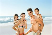 Parents carrying daughters piggyback on beach Stock Photo - Premium Royalty-Freenull, Code: 6113-07147719