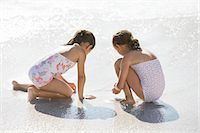Girls playing together in surf on beach Stock Photo - Premium Royalty-Freenull, Code: 6113-07147727