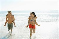 Parents carrying daughters piggyback in surf at beach Stock Photo - Premium Royalty-Freenull, Code: 6113-07147728