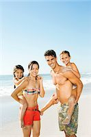 Parents carrying daughters piggyback on beach Stock Photo - Premium Royalty-Freenull, Code: 6113-07147776