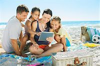 families playing on the beach - Family using digital tablet on beach Stock Photo - Premium Royalty-Freenull, Code: 6113-07147777