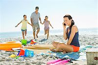 families playing on the beach - Woman talking on cell phone at beach Stock Photo - Premium Royalty-Freenull, Code: 6113-07147779