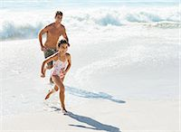 Father and daughter running in surf at beach Stock Photo - Premium Royalty-Freenull, Code: 6113-07147785