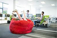 Businesswoman playing in beanbag chair in office Stock Photo - Premium Royalty-Freenull, Code: 6113-07147842