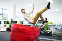 Businessman jumping into beanbag chair in office Stock Photo - Premium Royalty-Freenull, Code: 6113-07147991