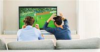 Men watching soccer game on sofa Stock Photo - Premium Royalty-Freenull, Code: 6113-07147998