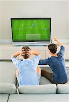 soccer fan - Men watching soccer game on sofa Stock Photo - Premium Royalty-Freenull, Code: 6113-07148003