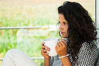 Teenage girl sitting next to window, holding cup in hands, Germany Stock Photo - Premium Royalty-Freenull, Code: 600-07148149