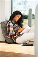 Teenage girl sitting on floor next to window and reading book, Germany Stock Photo - Premium Royalty-Freenull, Code: 600-07148151